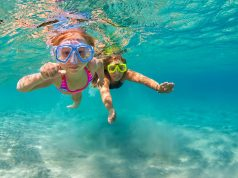 Happy family - mother with baby girl dive underwater with fun in