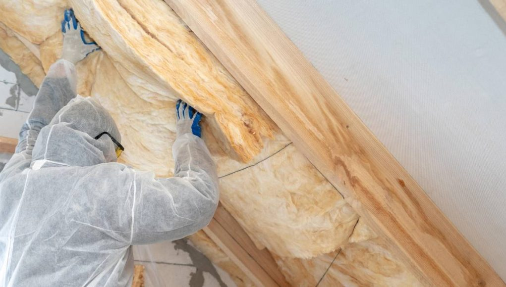 Professional workman in protective uniform installing thermal insulation layer under the roof.