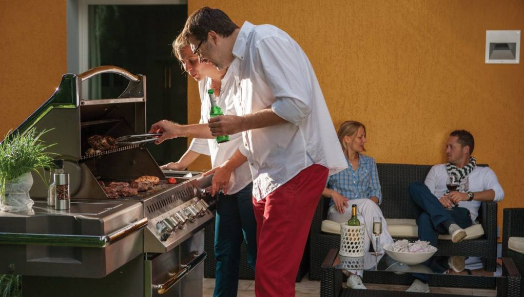 family grilling outdoors on patio